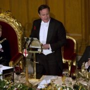 David Cameron calling for austerity while surrounded by gold, fine food and wine, and wearing a white bow tie.