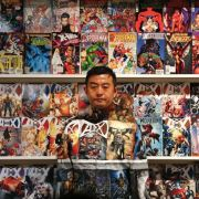 Liu Bolin, a Chinese artist, waits for the finishing touches to his camouflage, before being completely blended into the background, in front of a shelf lined with comic books.