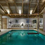 Indoor pool with a swing inside a chalet