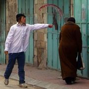 A jewish settler throwing wine at a Palestinian Woman