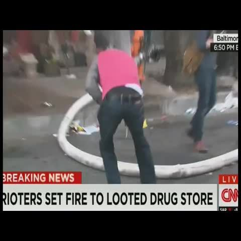 Baltimore rioter cuts a hole in firefighters hose as they try to put out a CVS fire that the rioters started.