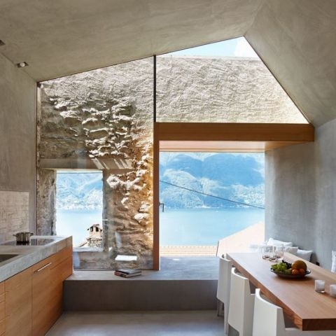 Kitchen and dining area look onto a lake in a completely restored stone home in Switzerland.