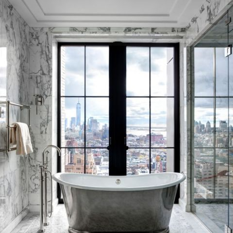 Silvered, free-standing bathtub overlooks Manhattan in the Walker Tower.