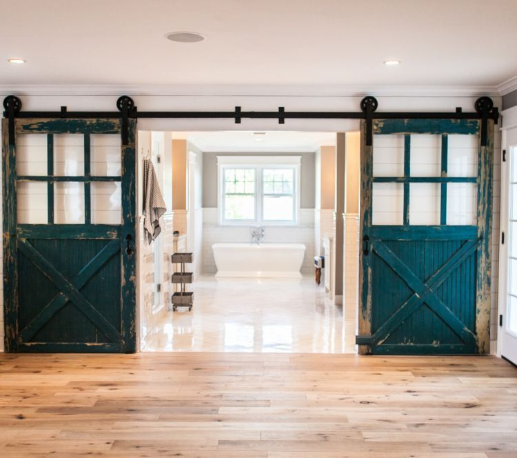 100-year-old carriage doors open onto the master bathroom in this home in Vermont.